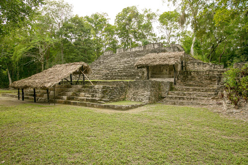 A rebuilt thatched roof in front of Edifice 13, also known as the Building of the Captives, at the Mayan ruins of Dzibanche in Mexico's Costa Maya region.