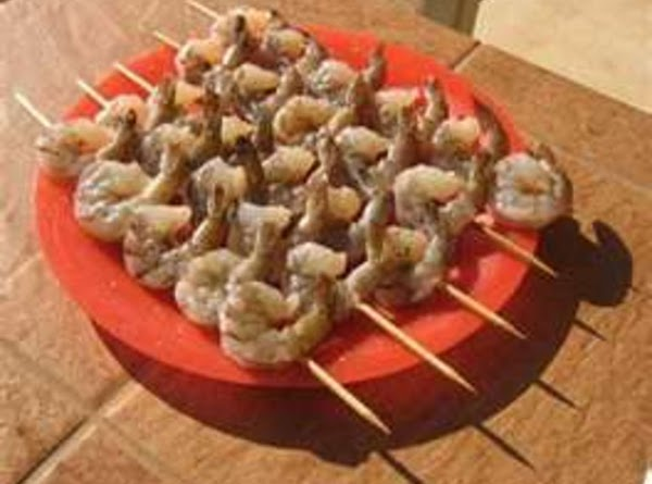 Thread Shrimp on wooden skewers. GRILL, Brushing and basting Shrimp with the remaining 1/4 Cup...