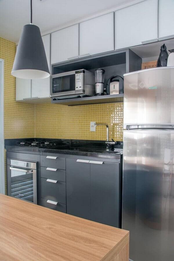 Cozinha com armário cinza e branco, geladeira de inox, bancada de madeira e pastilhas amarela na parede da pia.