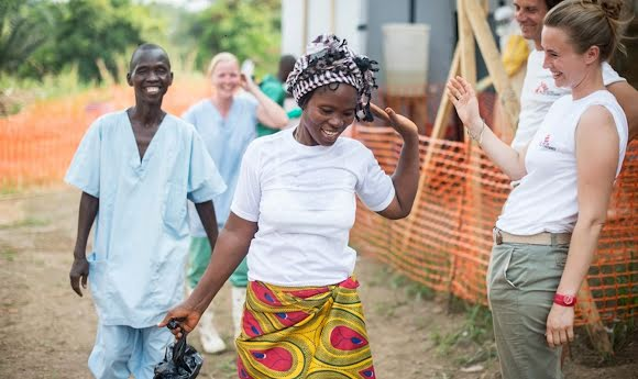 MSF volunteers laugh while sharing a joyful moment with an at-risk local.
