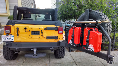 Photo: Rear tailgate on the Smittybilt Atlas rear bumper open, showing jerry cans and hi-lift jack position off of the bumper-mounted tailgate.  Rear door no longer has the tire attached.