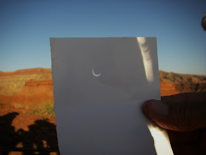 Photo: An image of the eclipse is projected through a small hole in a piece of paper through to another paper held at the right distance & angle to see the darkening sphere of light.