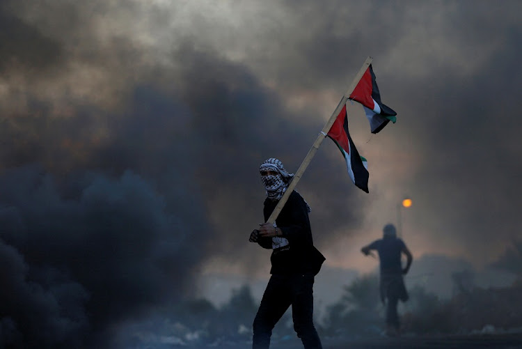 A demonstrator near the West Bank city of Ramallah holds a Palestinian flag during clashes with Israeli troops at a protest against US President Donald Trump's decision to recognize Jerusalem as Israel's capital, on Saturday. Picture: REUTERS/MOHAMAD TOROKMAN