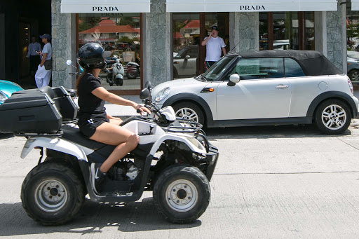 A young woman rides an ATV past trendy boutiques on the main street of Gustavia, St. Barts.