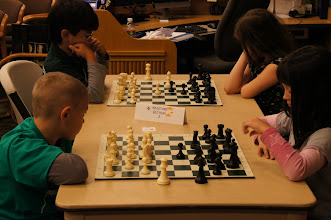 Photo: Rising Stars, seciton J Ella Flett finishes castling in her second round game against Ethan Booth, who looks more interested in Mcya Allyn in her game with Kai Schlegelmann