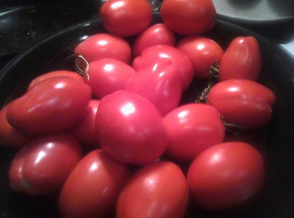 Wash and score your tomatoes by making a slit across the bottom like an...