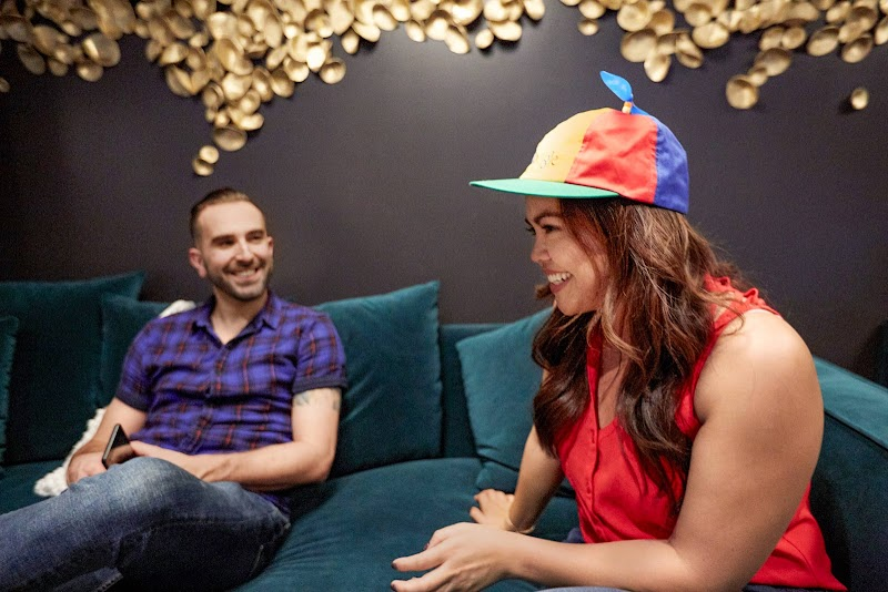 Person in blue shirt and person wearing Google pinwheel hat seated on couch smiling and talking to each other.