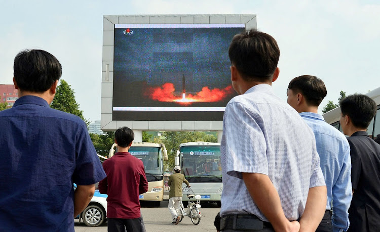 North Koreans watch a news report showing North Korea's Hwasong-12 intermediate-range ballistic missile launch on electronic screen at Pyongyang station in Pyongyang, North Korea. Picture: REUTERS