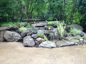 Photo: Check out these stunning Aquascape Pondless Waterfalls in Brighton NY Designed for this Outdoor Garden Room by Acorn Ponds & Waterfalls, Certified Aquascape Contractor, Pond Designer, #LandscapeDesigner of Rochester NY.  Check out our website www.acornponds.com and give us a call 585.442.6373.  This Backyard Outdoor Room included a Paver Patio Design and Installation, Pillars with Sitting Wall, LED Landscape Lighting, Low Maintenance Plantings, Aquascape Pondless Waterfalls and Stream. The Patio was pitched to capture and store the Rainwater in the #Pondless Waterfall Basin. The homeowner hardly ever need to even add water! The LED Landscape Lighting adds hours of enjoyment and so economical to run.  Interested in a Waterfalls without the pond? Please click here: www.acornponds.com/pondless-waterfalls.html  To learn more about Susan & Bob's incredible Backyard Transformation please click here: www.facebook.com/notes/acorn-landscaping-landscape-designlightingbackyard-water-gardens/backyard-waterfalls-water-feature-paver-patio-landscaping-landscape-design-brigh/421691824534612  For more info about Acorn Ponds & Waterfalls Services, please click here: www.acornponds.com/services.html  Acorn Ponds & Waterfalls of Rochester NY, 585-442-6373, is a Certified Aquascape Contractor, Landscape Designer, Outdoor Lighting Designer, Installer, Builder, Contractor and Design Service Company from Rochester, NY. We have professional Installation and Design Services available for the following: Landscape Design Outdoor Room Design Backyard Ponds and Waterfalls Design & Construction Patios and Walkways: Paver, Stone, Brick Low Voltage Landscape Lighting LED Landscape Lighting Swimming Ponds Ecosystem Ponds LED Outdoor Lighting Retaining Walls Fountains Water Features Pondless Waterfalls Pond Maintenance and Design Aquatic and Under Water LED Lights Bubbling Boulders and Urns Natural Stone Patios and Rock Gardens Garden Ponds Outdoor Kitchens Pizza Ovens Fire Pits Fish or Koi Po