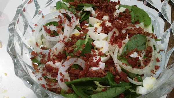 To the dressing, add the onion, spinach, lettuce, bacon and chopped whites. Toss well...