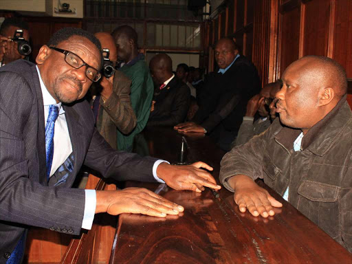 Lawyer James Orengo consults with Governor Sospeter Ojaamong at a Milimani anti-corruption court.