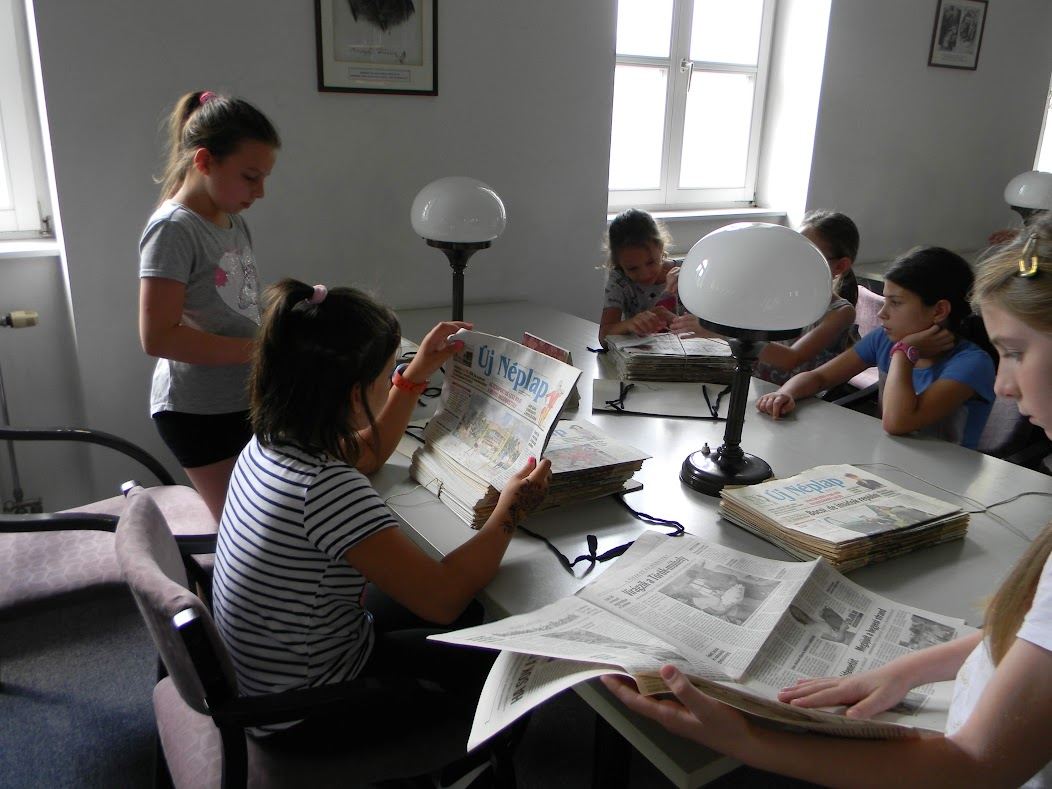 Újságot olvasó gyerekek