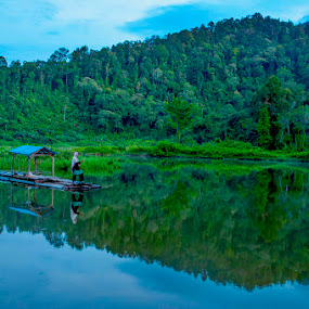 A fisherman on the lake in the morning by Ian Bismarkia - Landscapes Waterscapes