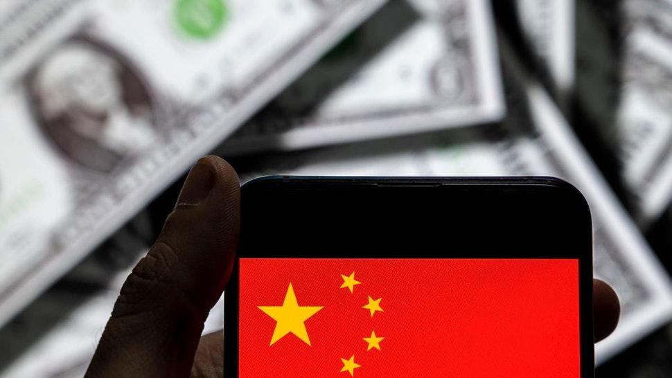 In this photo illustration the People's Republic of China flag logo seen on an Android mobile device screen with the currency of the United States dollar icon, $ icon symbol in the background.