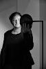 vrouw in zwart kijkt deels in en deels naast ronde, verlichtte, spiegel