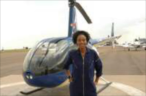 FLYING RIGHT: Khosini Ngobese has only 20 hours of flying to go to get her licence from alphine Aviation School at Grand Central Airport. Pic. Tsheko Kabasia. © Sunday World.  CHALLENGING JOB: First black, female commercial pilot, Khosini Ngobese, who works for the South African Civil Aviation Authority inspecting helicopter operations in the country, poses next to one of the aircraft she flies. Sunday World. 06/01/2008. Pg 29.