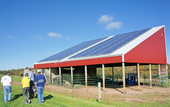 Photo: Hugh Smith, the owner, shows Joanie, Vern, and Randy Clear Spring Farm's 24.5 kW solar photovoltaic array, which sits on the roof of their yak barn.