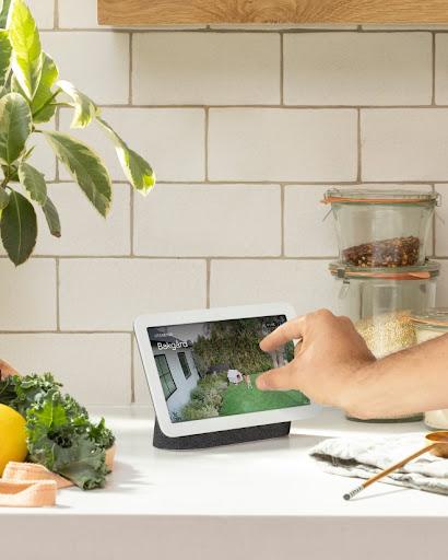 Nest Hub-skärm på ett bord visar ett klipp från kameraflödet