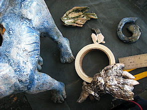 Photo: glueing 'Paradox' the sphinx back together for the second time This sculpture has been a learning experience, the wire armature I used in his wings and tail melted in the bisque and then the metal flowed into the cracks. I filed the metal off of the deformed chunks and raku fired him. He fell apart again, but it was in less pieces, as some of the broken parts were glazed together with molten glass in the raku.