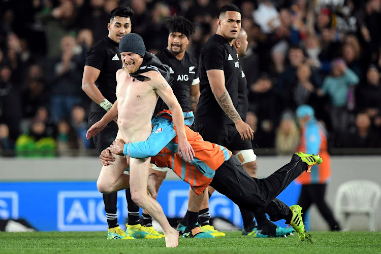 A security guard tackles a streaker during Saturday's New Zealand v France rugby match in Auckland.