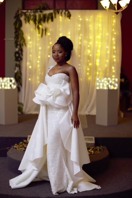 Sphilile (Tee Xaba)'s bridal gown featured a detachable overskirt which gave the effect of a train as she walked down the aisle.