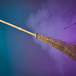 Floating broomstick and wand shrouded in smoke