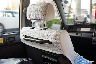 Photo: All taxis on Okinawa have the same seat covers. The doors opens automatically even though the cars are old style.