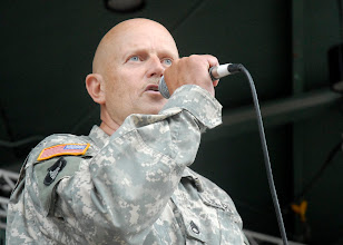 "Photo: Staff Sgt. Terry Kamp narrates ""I am the Nation"" during the performance of ""America the Beautiful"" by the 34th Red Bull Infantry Division Band at the Minnesota State Fair's Military Appreciation Day Aug. 30, 2011 in St. Paul, Minn."