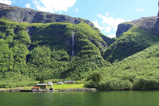 Norway-Naeroyfjord-farm - A farm on Naeroyfjord is backed by a dramatic waterfall.