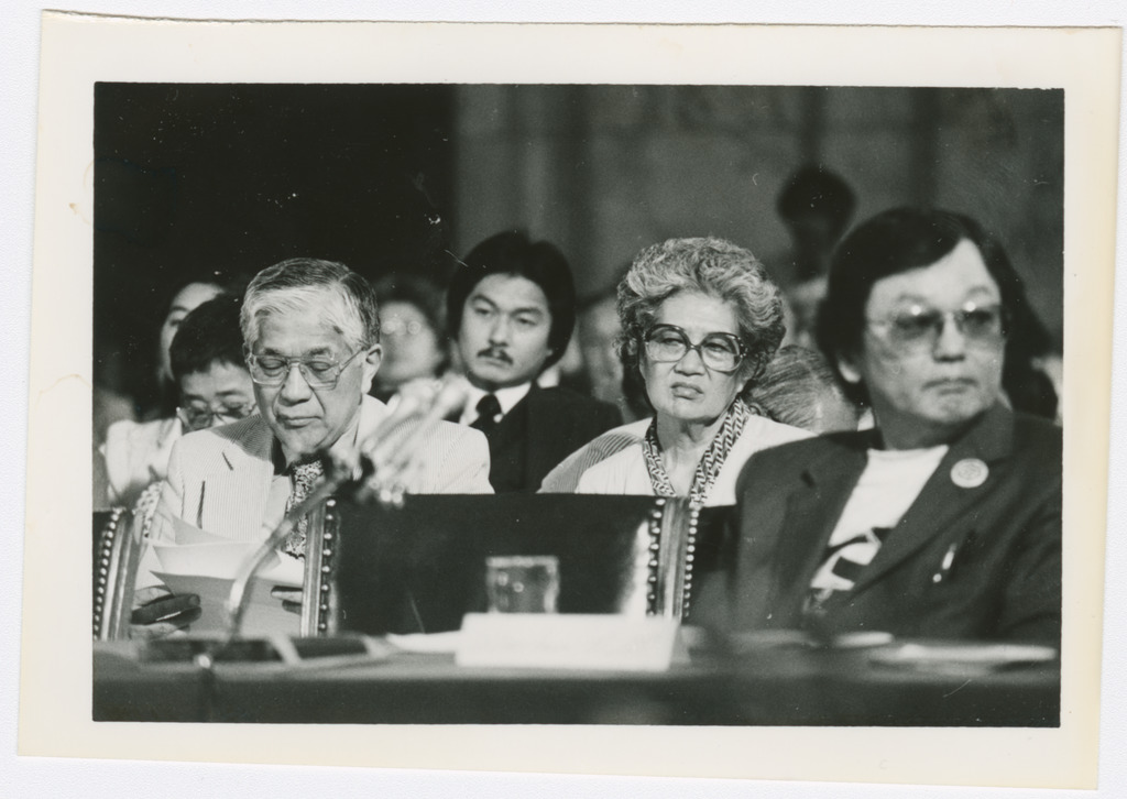 Aiko Herzig-Yoshinaga and others seated in the hearings and listening to testimony.