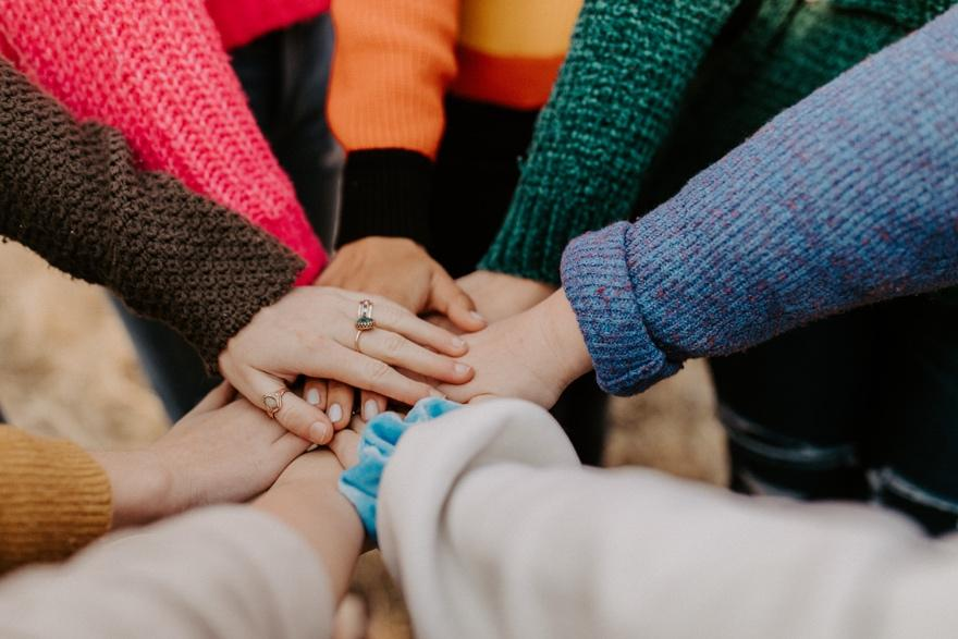 A close-up of people holding hands  Description automatically generated with medium confidence