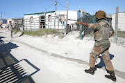 As the infection rate in Cape Town soared, a soldier in Khayelitsha orders a resident to return to his home and stay there in accordance with the regulations.