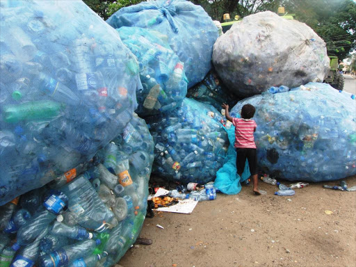 A child standing next to a pile of plastic bottles.