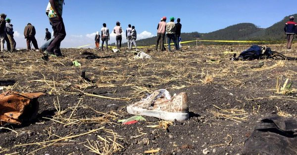 People walk at the scene of the Ethiopian Airlines Flight ET 302 plane crash.