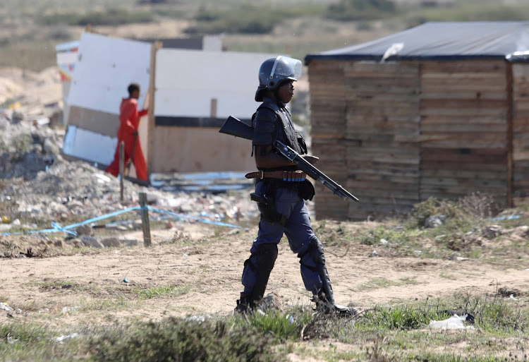 A public order policeman armed with a shotgun stands guard as shacks are demolished in Dunoon, Cape Town, on April 25 2019.