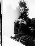 portret van een man, zittend achter een ruit met weerspiegeling van betegelde tuin