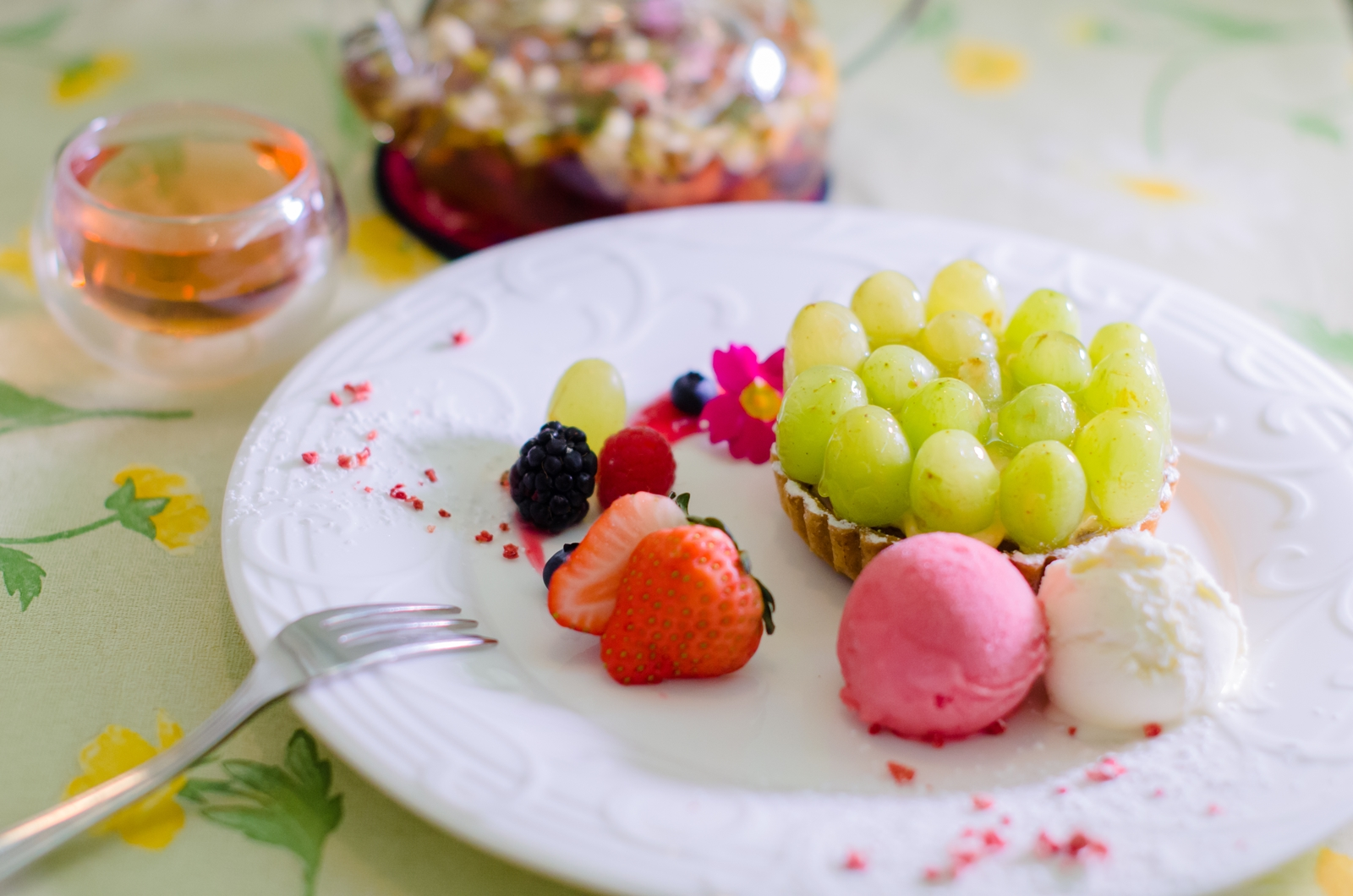 Photo: 「タルト・トンプソン」 フランス菓子 エリティエ  皮ごと食べられるブドウ トンプソンがたっぷりと敷き詰められたタルトです♪  薄めの皮は 噛むとパリッとはじけて、 果肉はしっかりと歯ごたえがありつつも じゅわっと果汁が口に広がります。 甘みがとっても 爽やかな気持ちにさせてくれますね☆ 程よい甘みのカスタードも敷かれて 口の中で合わさると いっそう味の深みを増してくれます!  パナッシェセットで オリジナル花茶と合わせていただくと とても優雅なティータイムを楽しめます♪  また現在エリティエさんでは チーム北海道という北海道に通じる17名の写真家集団による写真展 「きたのくにから2016~大地のおくりもの~」 という写真展も開催されています。 北海道の雄大な自然、 そしてそこに住むいきもの達、 今なら美味しいスイーツを楽しみながら、 そんな北海道の空気も楽しむことができます♪  写真展の会期は6月24日(金)まで、 この機会にぜひぜひ訪れてみてください☆  イベントページ 「 きたのくにから2016~大地のおくりもの~」 https://plus.google.com/u/0/events/cs3cm9efdf549psjnpmop7vanvs  「 フランス菓子 エリティエ 」 http://heritier-jp.com/  Nikon D7000 Nikon AF-S NIKKOR 50mm f/1.4G  #ケーキの日 #ごちそうフォト ( http://takafumiooshio.com/archives/2431 )