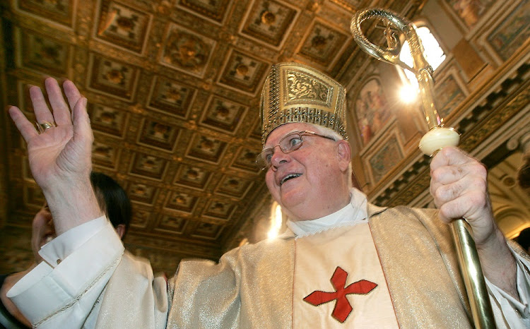 Cardinal Bernard Law waves to the faithful at the end of a ceremony for Our Lady of the Snows, in the Basilica of St. Mary Major in Rome, August 5, 2004.