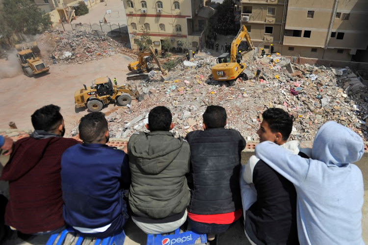 Rescuers work at the site where a building collapsed in Gesr al-Suez, Cairo, Egypt, on March 27 2021.