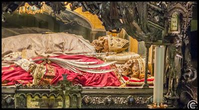 Photo: Krypta der Basilika Sant´Ambrogio Der heilige Ambrosius, gestorben am Vorabend von Ostern 397, mit Mitra liegt erhöht zwischen den beiden Märtyrern Gervasius und Protasius (Zu den Attributen des Heiligen zählen das Geißel und die Keule, sowie die Märtyrerkrone).  Die Verehrung des Heiligen als Schutzpatron der Imker erklärt sich aus einer Überlieferung, der zufolge sich in der Kindheit des Heiligen ein Bienenschwarm auf seinem Gesicht niedergelassen haben soll. Die Bienen seien in den Mund des Kindes gekrochen und hätten es mit Honig genährt. Dies wurde als Zeichen Gottes und ein Hinweis auf eine große Zukunft des Kindes gedeutet. Bienen werden wegen ihres seit jeher wertvollen Honigs und wegen des Wachses, des über Jahrhunderte einzigen Materials für die Kerzenherstellung, im Gesang des Exsultet geehrt und gelten sowohl als Christussymbol wie als Symbol der geweihten Jungfrauen und des Fleißes. In Österreich ist der 7. Dezember wegen des Gedenktags des Heiligen auch Tag des Honigs.