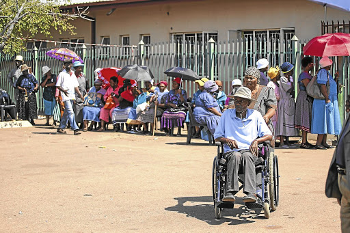 Recipients queue to collect their their grant money. Picture: ALAISTER RUSSELL