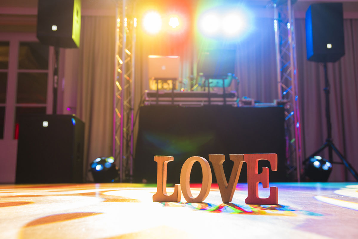 Love Letters Sign on the dance floor with DJ equipment and lighting effects
