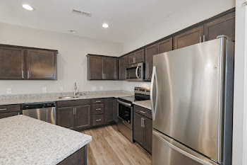 Bailey Grand kitchen with dark cabinets and stainless steel appliances