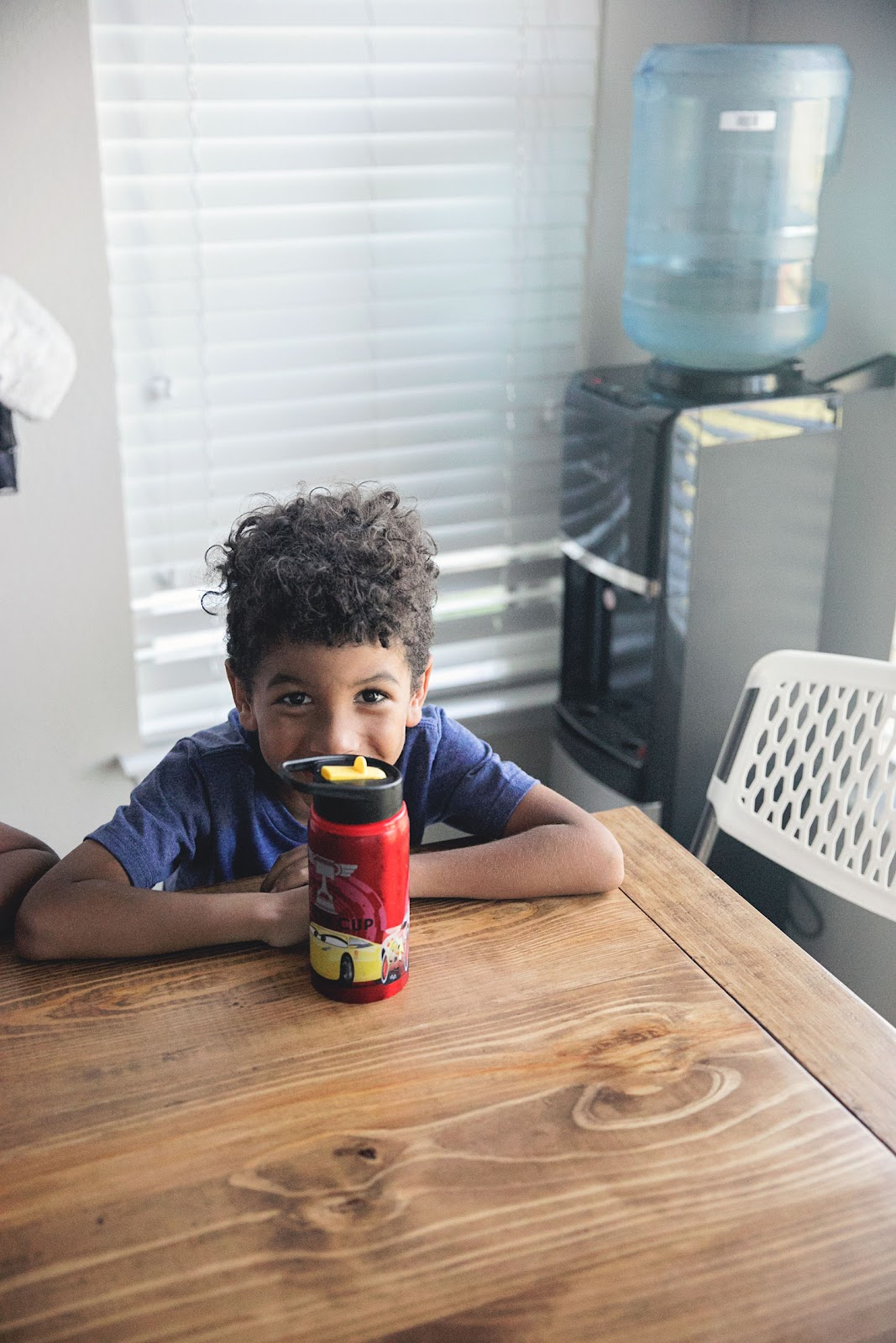 Boy sitting at kitchen table with a water bottle. Primo water best water dispenser.