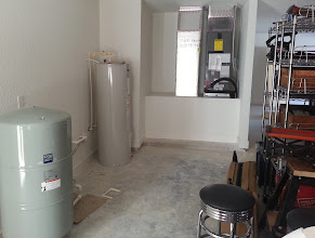 Photo: December 19, 2012 Inside the garage. Some of our stuff piled up on the right with some of the water handling stuff on the left. The water heater looks somewhat oversized because it is. Filtration and conditioning equipment still need to go in.