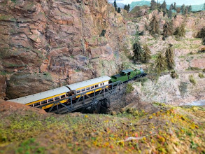 Photo: 014 This huge 2-.6-6-2 Mallet tender loco and train of Jim Hurley's scratchbuilt coaches is dwarfed by the grandeur of the rocky mountainous landscape .