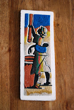 Photo: Winning Shell Number: 496  10. Sand painting on wood depicting a woman carrying a baby making a sort of cous cous