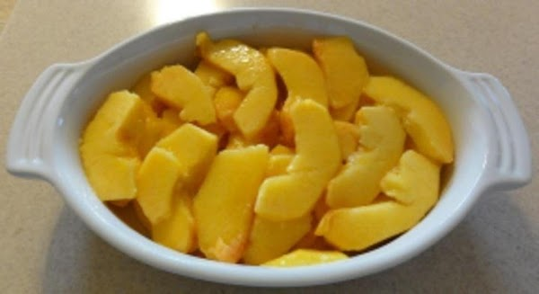 Add the sliced sweet peaches to a baking dish.
