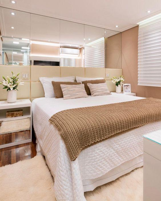 Quarto com cama de casal com cabeceira estofada e espelho de fundo, tapete em tom neutro e criado mudo branco.