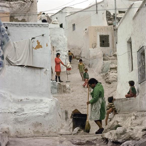 La vida bulle en el barrio con las mujeres barriendo y los niños subiendo y bajando la cuesta. La instantánea es de 1962.